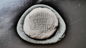 A stone with the words inscribed in clay in runic script: Hurrian Cult Legacy
